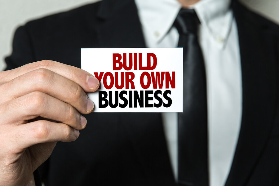 "Picture of a man holding a sign that says ""build your own business and become self employed."""