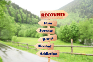Image of a road sign with the caption reentry programs, addiction, housing, recovery and help.