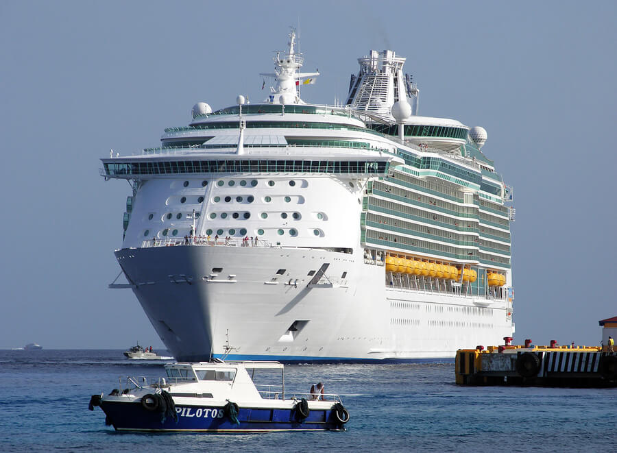 Picture of a cruise ship arriving at a port in a foreign country.