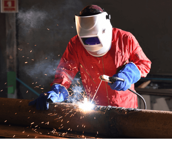 Image of a man stick welding a pipe. He is wearing a leather welding jacket and welding helmet.