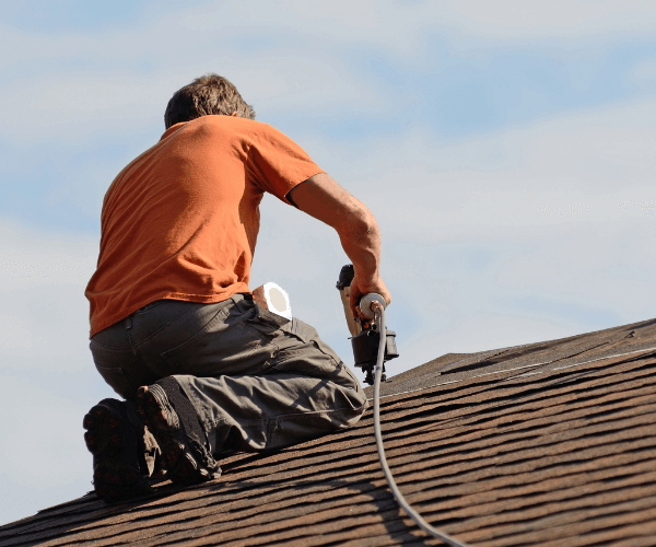 Image of a roofer on top of a roof replacing shingles.